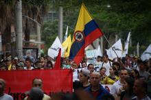 People marching, one holding big Colombian flag